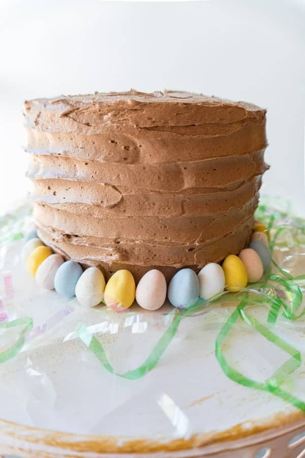 This fun and Easy Easter cake will satisfy any sweet-tooth! An amazing yellow cake recipe, with vanilla and chocolate buttercream frosting- it is out of this world good! #easter #yellowcake #cakedecorating #easy #homemade #fromscratch #atablefullofjoy #dessert