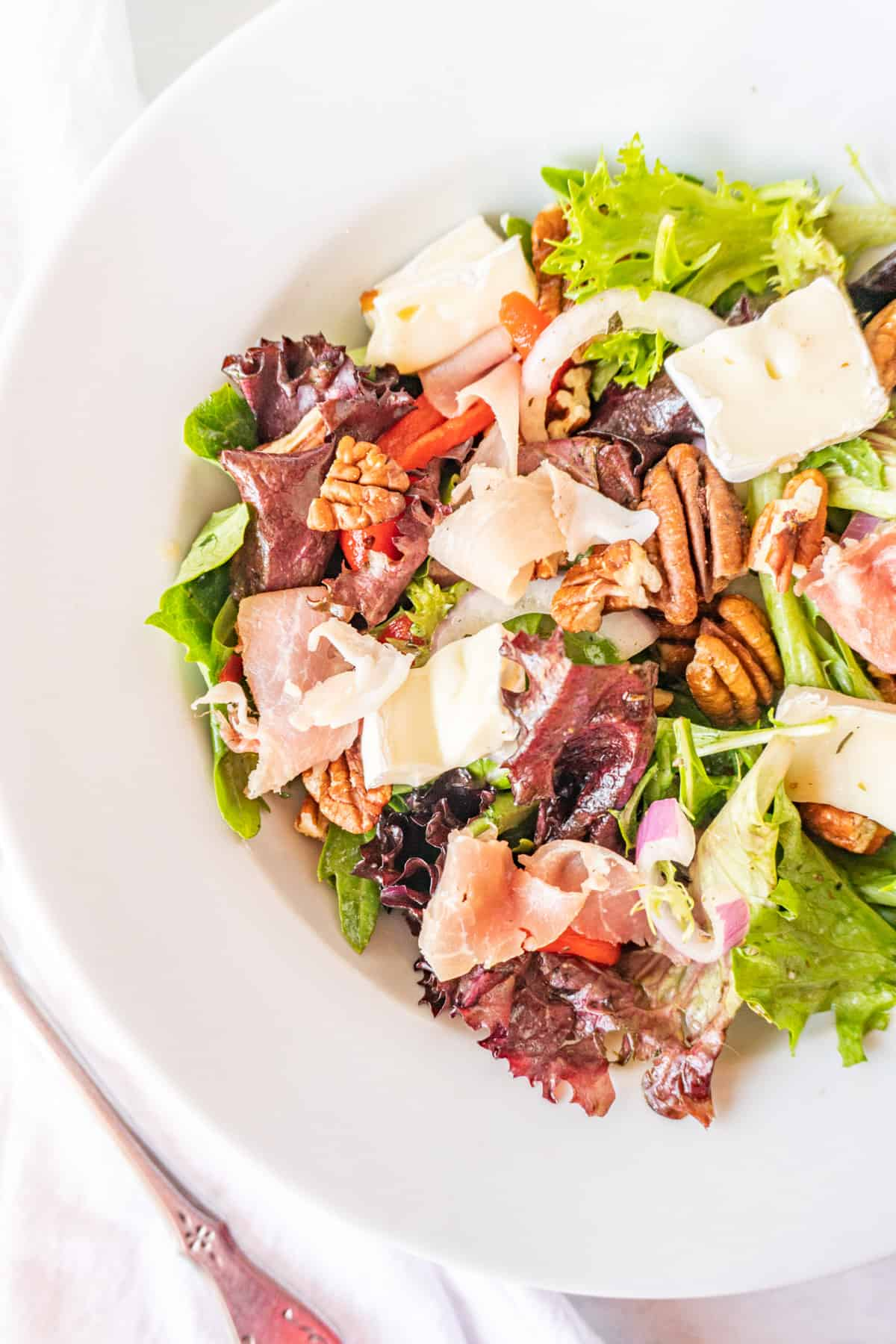 white salad bowl filled with salad mix, prosciutto, brie, red onion