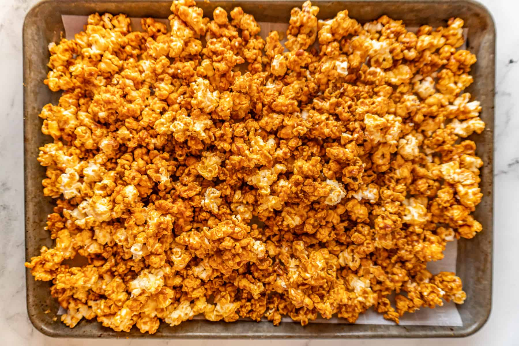 buffalo popcorn on baking sheet