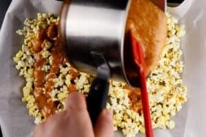 pouring caramel over popcorn on baking sheet