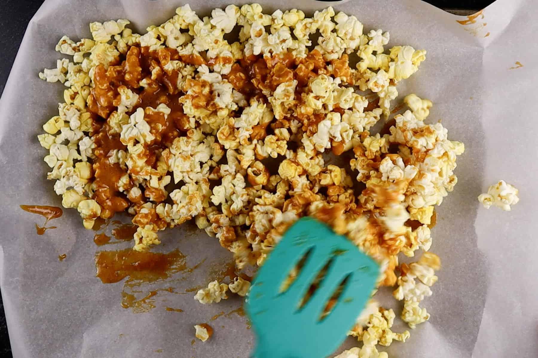 stirring popcorn on baking sheet