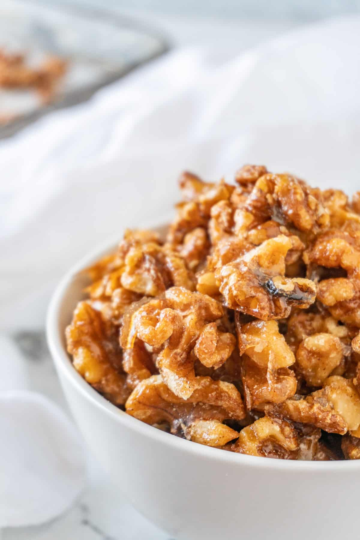 candied walnuts in white bowl close up