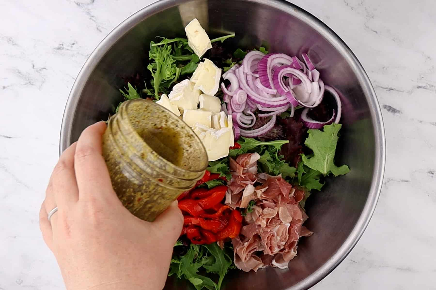 adding dressing to large bowl with salad ingredients