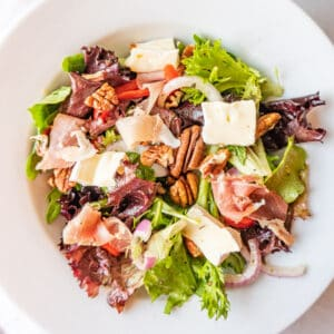 white salad bowl filled with salad mix, prosciutto, brie, red onion featured image