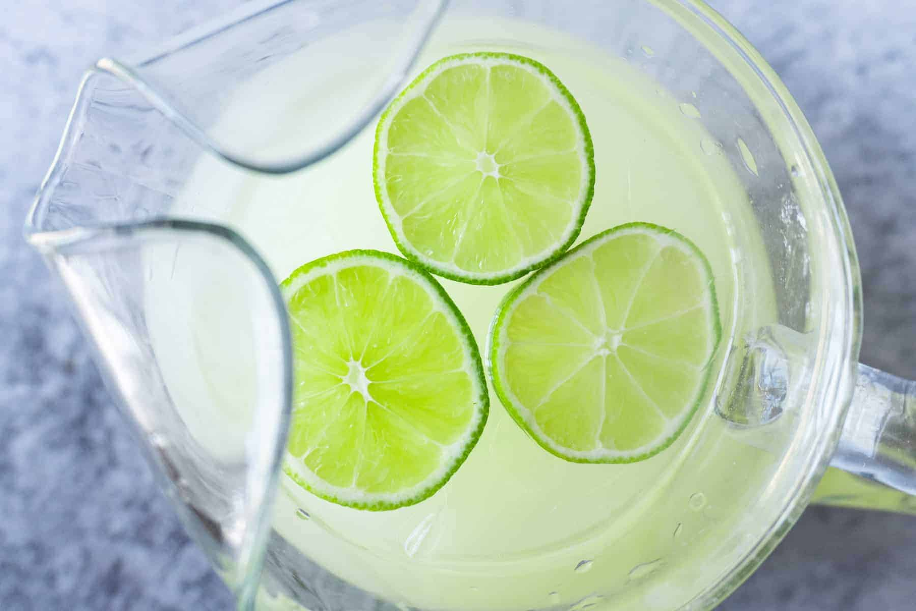 Pitcher of limeade with lime wedges