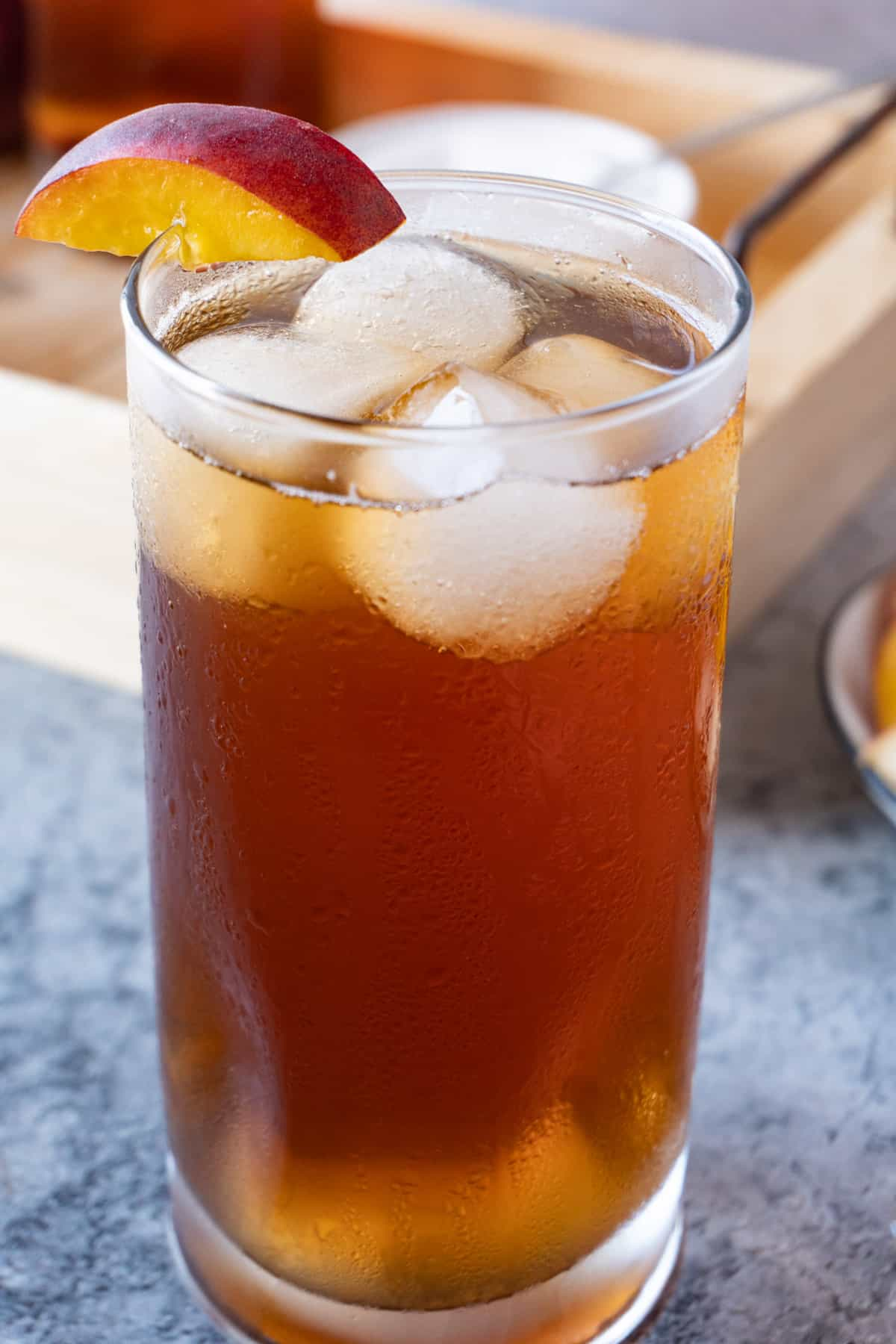 peach iced tea in glass with ice cubes