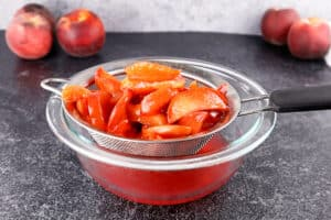 strainer with peaches in it and syrup in bowl beneath