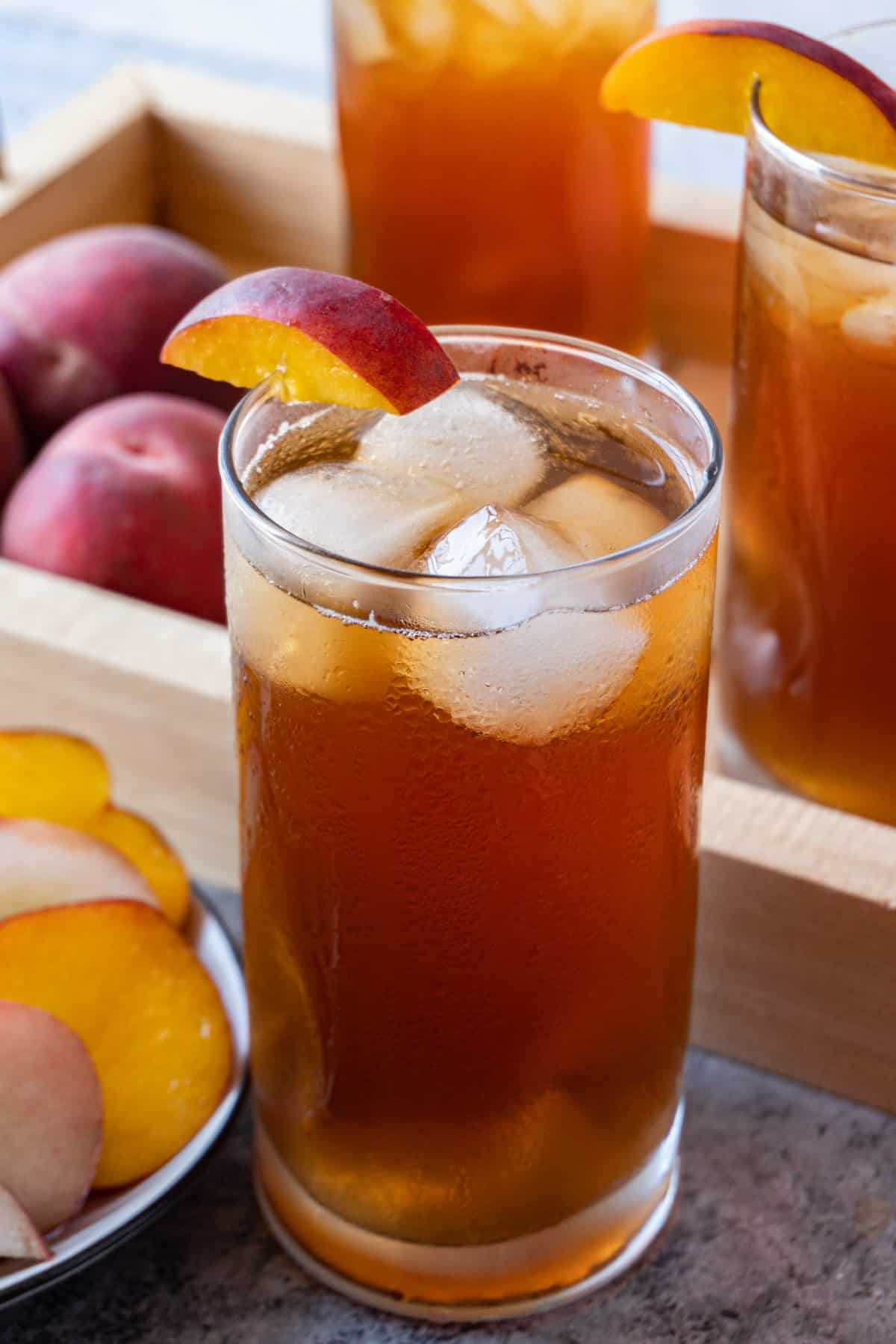peach tea in glass with ice cubes and peaches in background