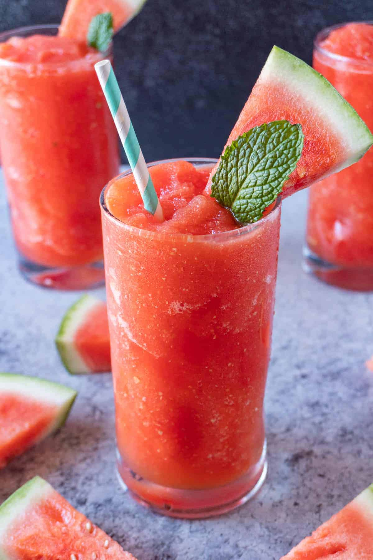 Watermelon Slushie in cup with watermelon slice and mint leaf sticking out