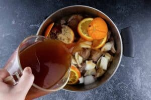 Adding broth to cooking pot