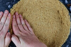 pressing the graham cracker crust into the the pie dish