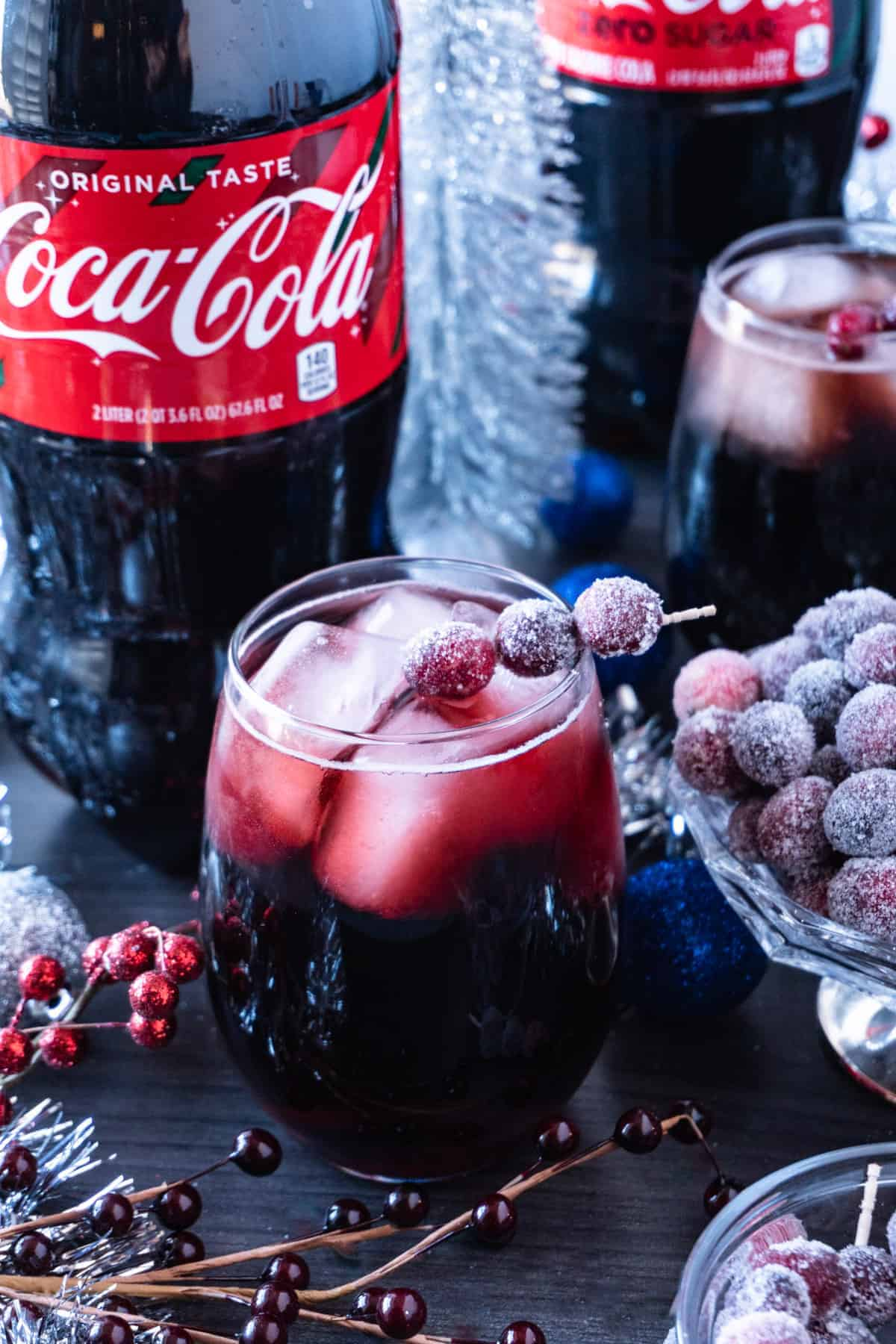 Easy Christmas Drink with coke bottle and sugared cranberries in background