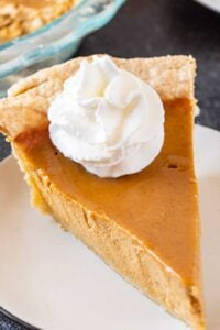 clos eup of slice of pumpkin pie with whipped cream