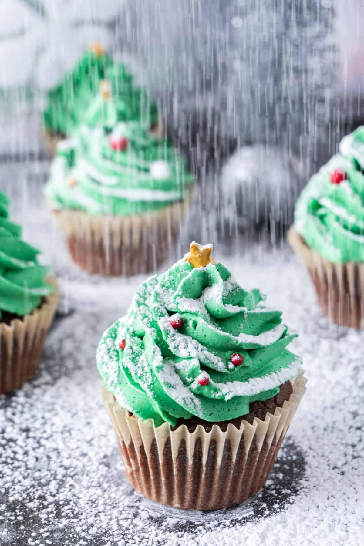 "Christmas Tree Cupcakes with powdered sugar ""snowing"" on them"