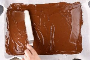 spreading the chocolate onto a baking sheet