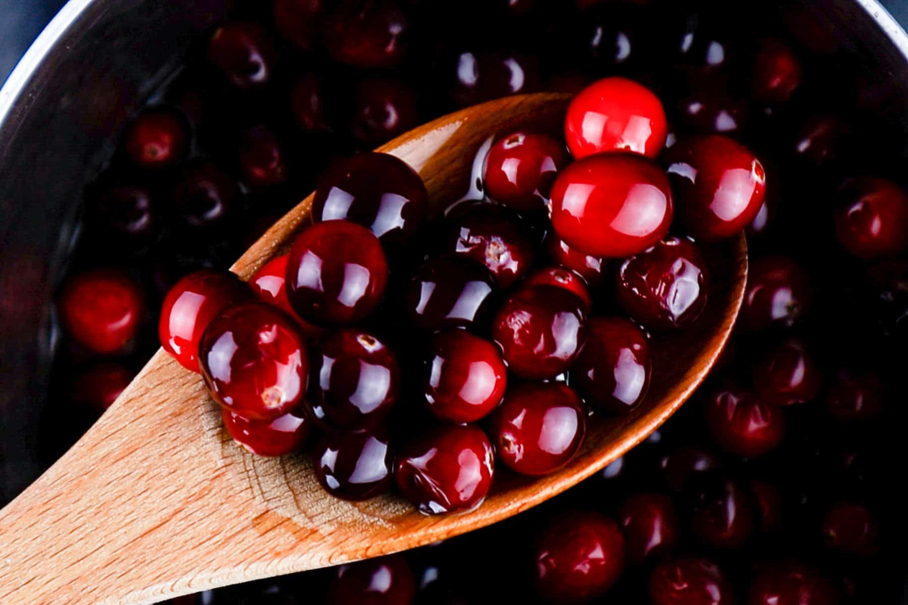 coated cranberries in sugar syrup on wooden spoon