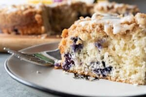 Blueberry Coffee Cake, An easy and delicious blueberry coffee cake that is perfect year-round! Topped with lots of crumb topping and a yummy glaze- you can't go wrong with this blueberry coffee cake! #coffeecake #bisquick #homemade #blueberry #recipes #cinnamon #easy #atablefullofjoy