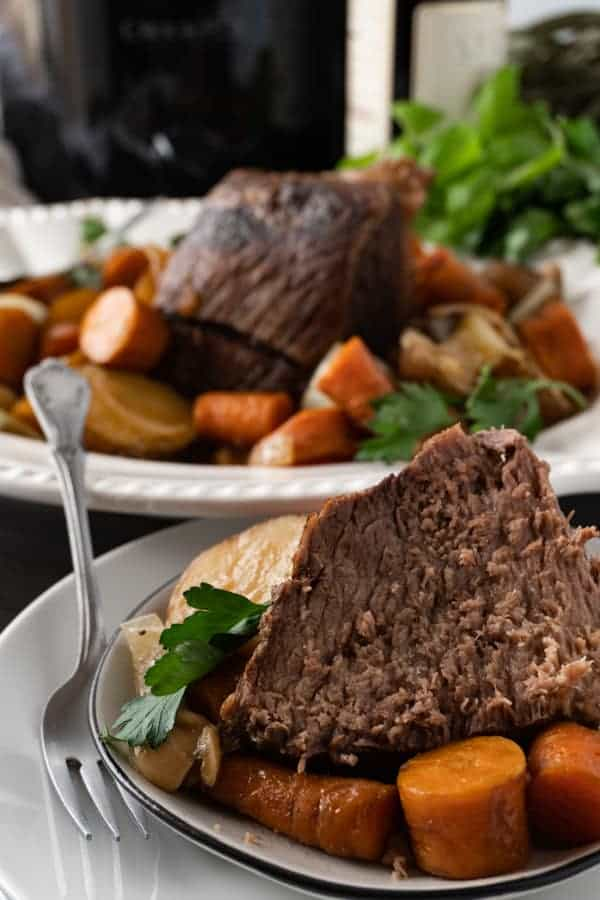 Crock Pot Pot Roast cut ontop of carrots and potatoes