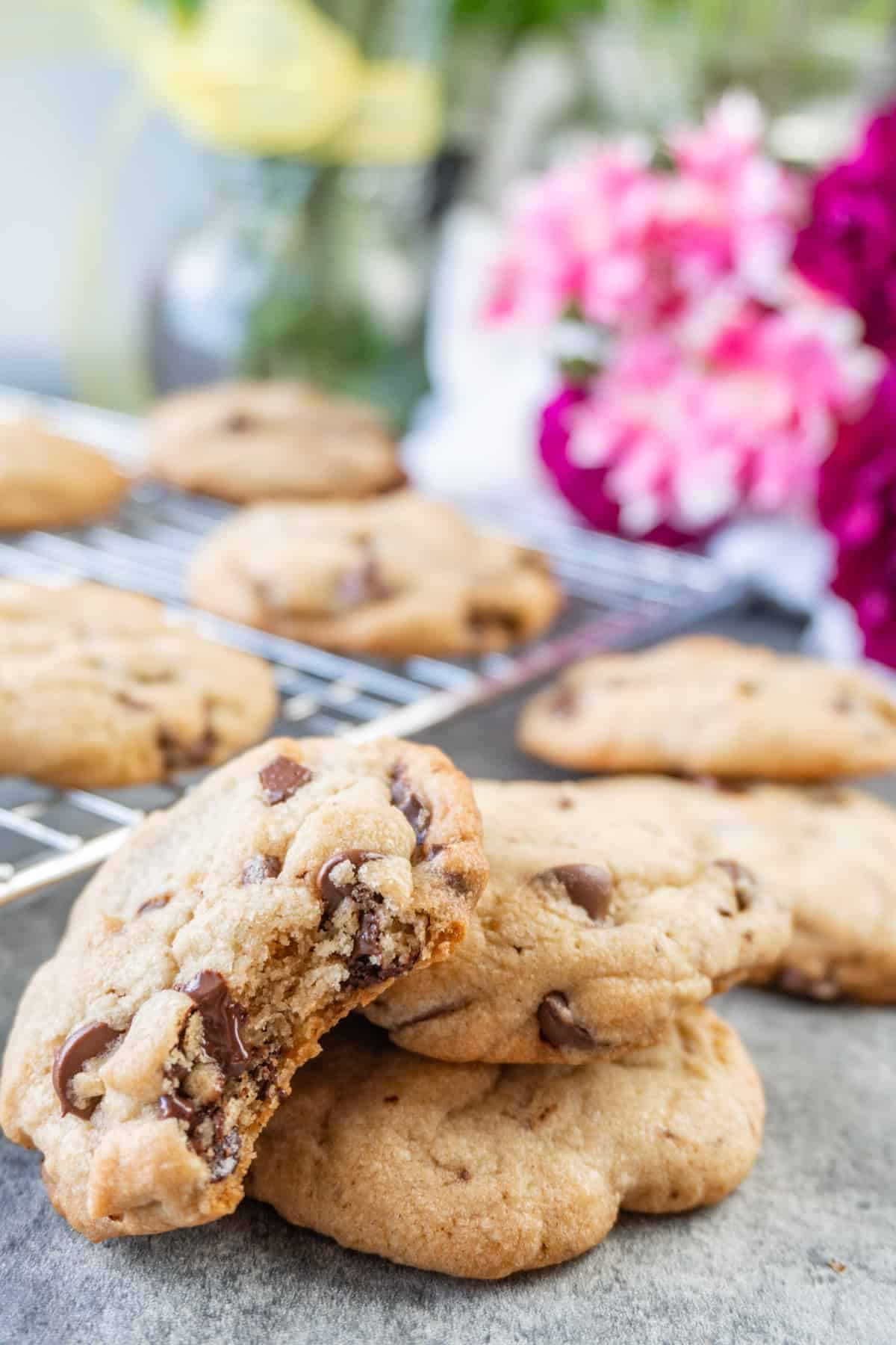 chocolate chip pudding cookies with bite taken out, flowers and cookies in background