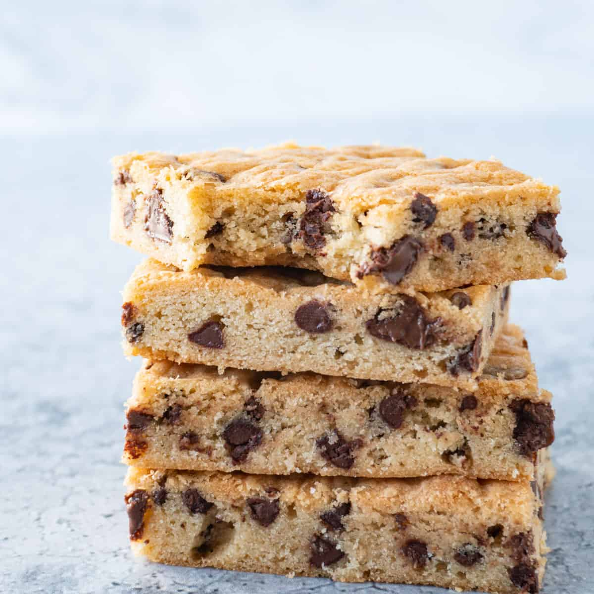chocolate chip cookie bars stacked with bite taken out of top featured image