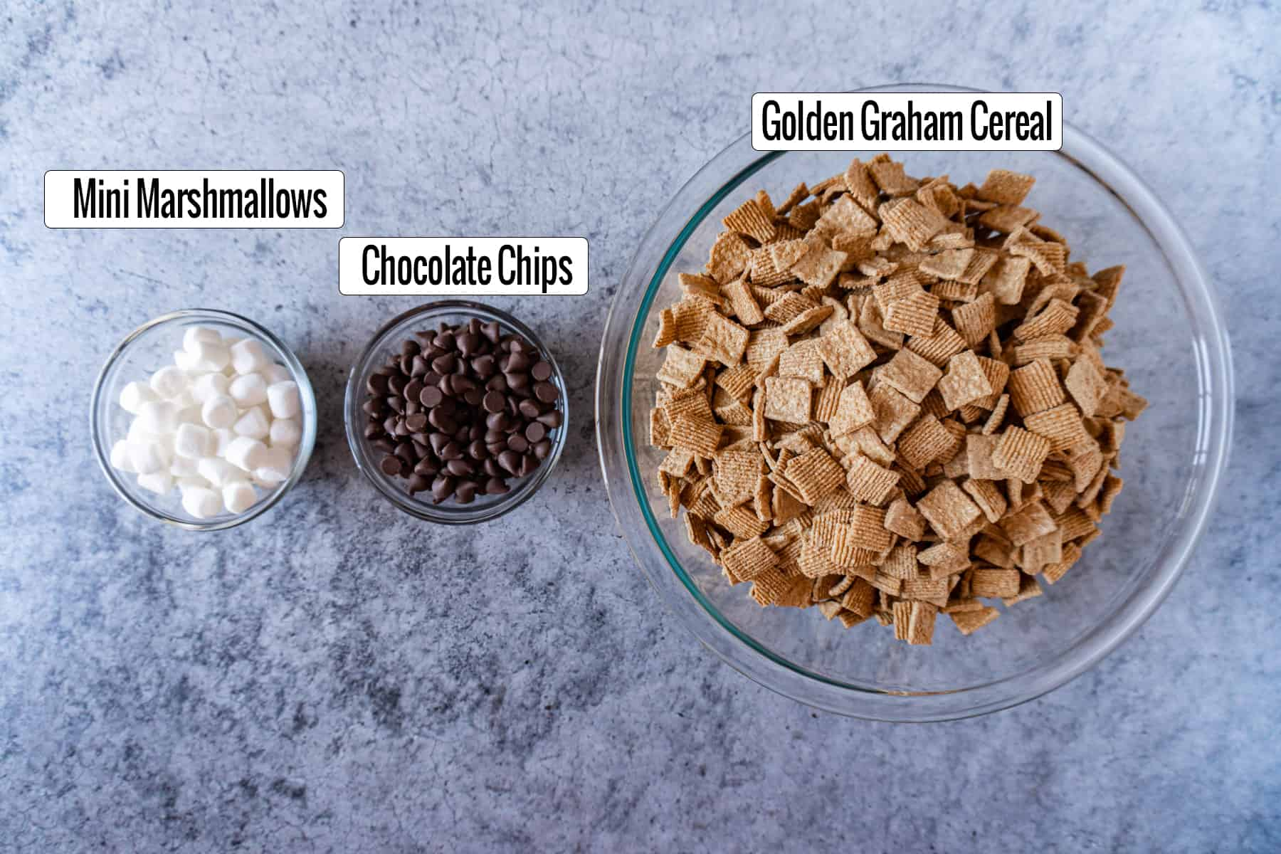 ingredients in bowls- golden graham cereal, chocolate chips, marshmallows