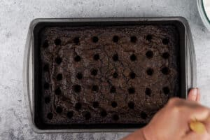 poking holes in baked brownies with wooden spoon handle
