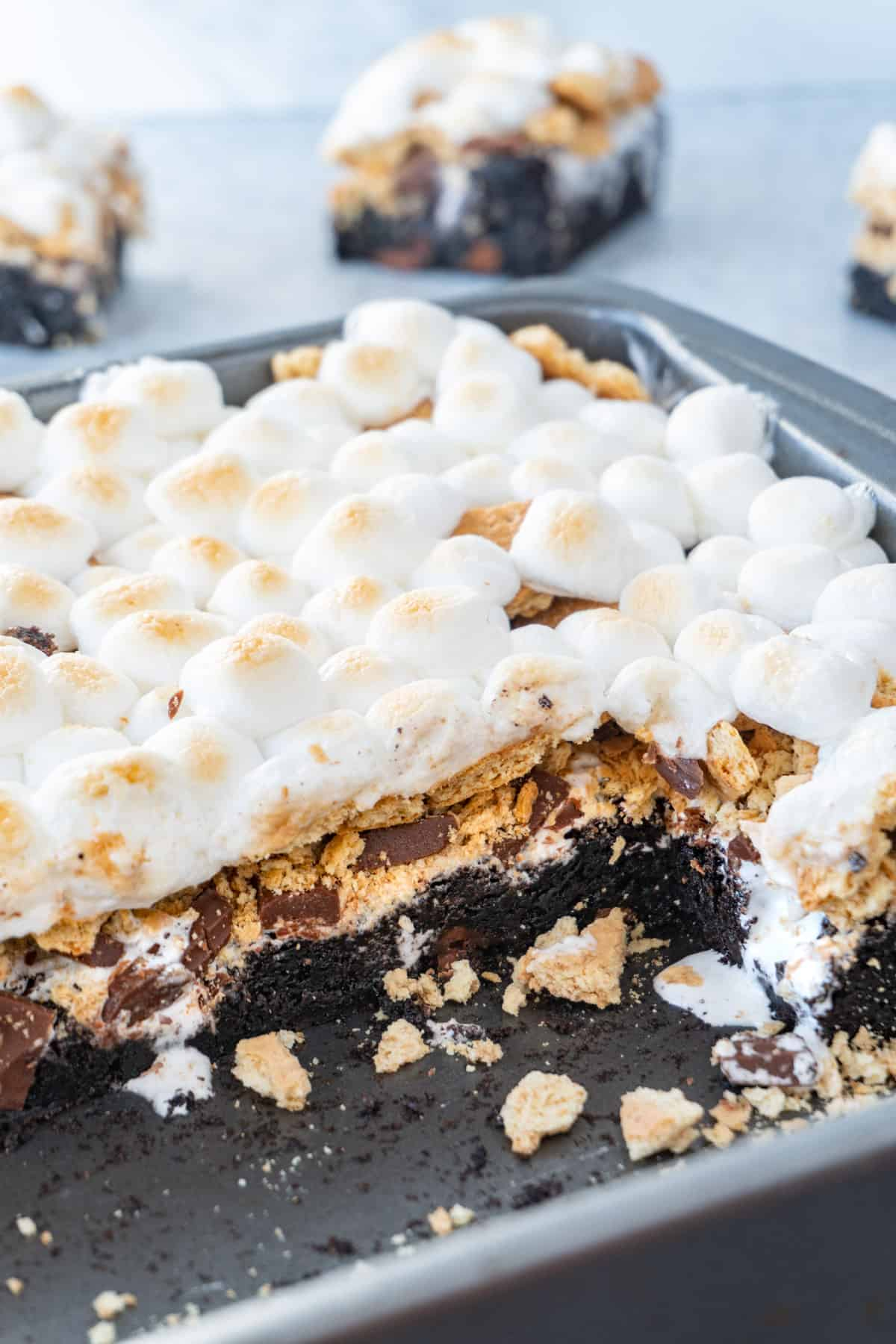 pan of s'more brownies showing layers of brownie, chocolate, marshmallow