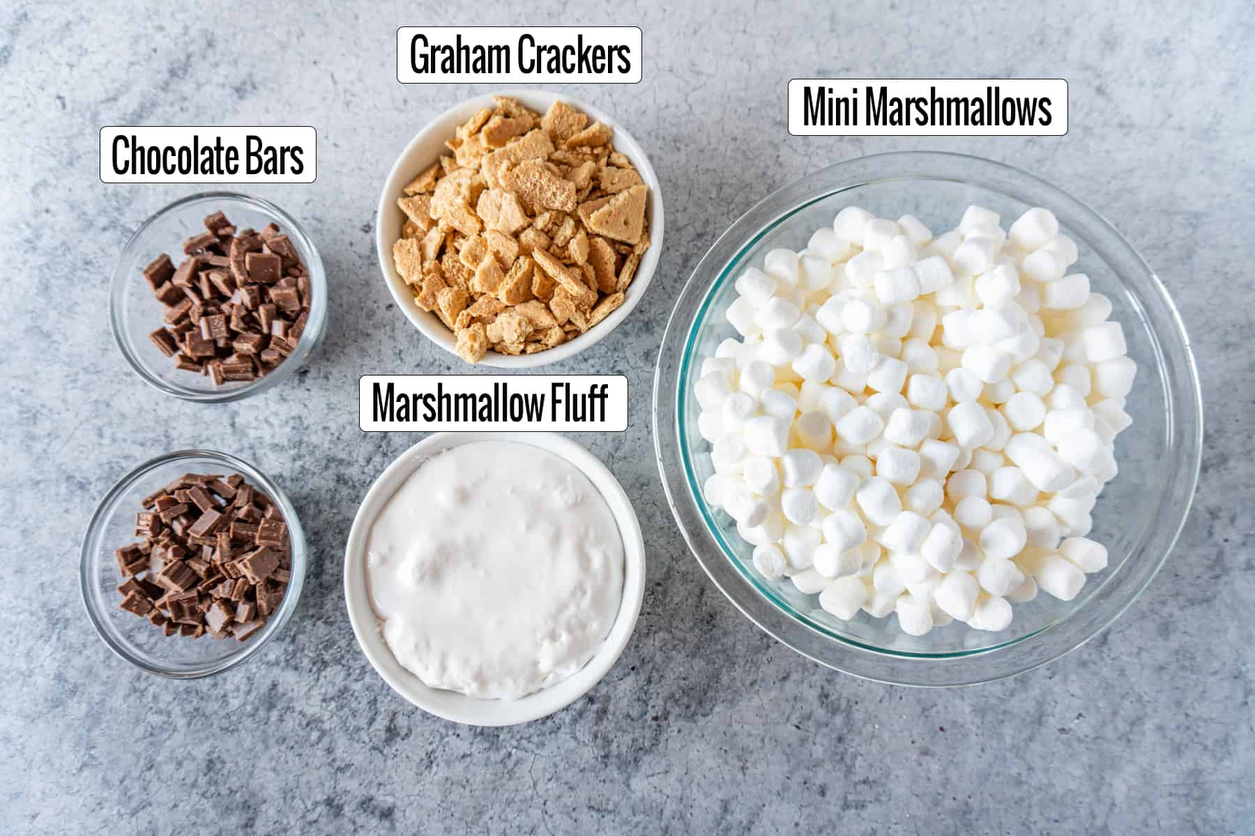 ingredients in bowls: Chocolate pieces, crushed graham crackers, marshmallow fluff, and mini marshmallows