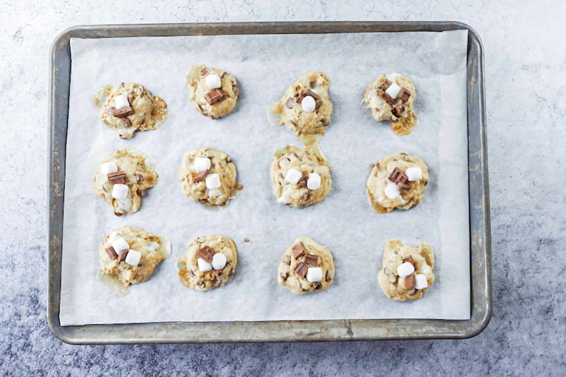 adding more marshmallows and chocolate to partially baked cookies