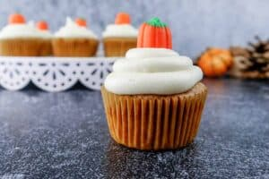 pumpkin cupcake with cream cheese frosting with cupcakes in background