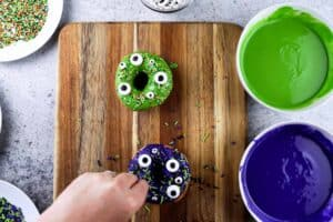adding eyes and sprinkles to monster donuts