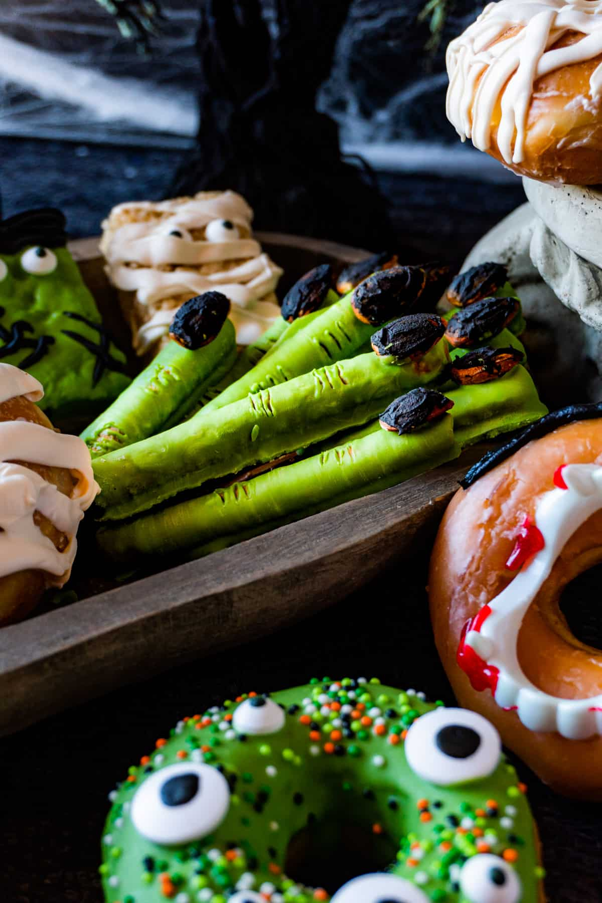 witches fingers in a snack board with other halloween snacks