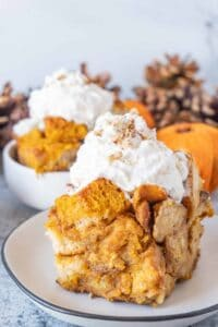 Close up of slice of pumpkin bread pudding with whipped cream on top