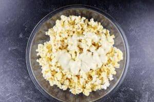 adding white chocolate to popcorn