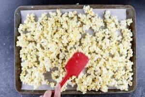 spread popcorn on baking sheet