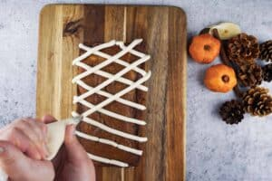 Frosting the pumpkin in a criss cross pattern