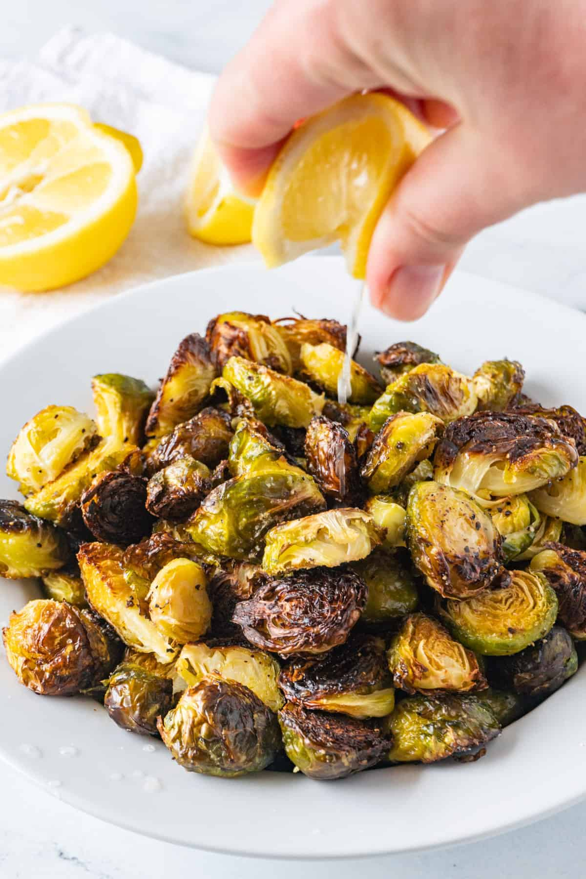 Oven Roasted Brussel Sprouts with lime juice being squeezed onto them