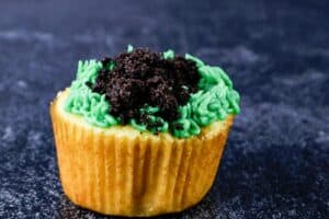adding crushed oreos on top of grass frosting