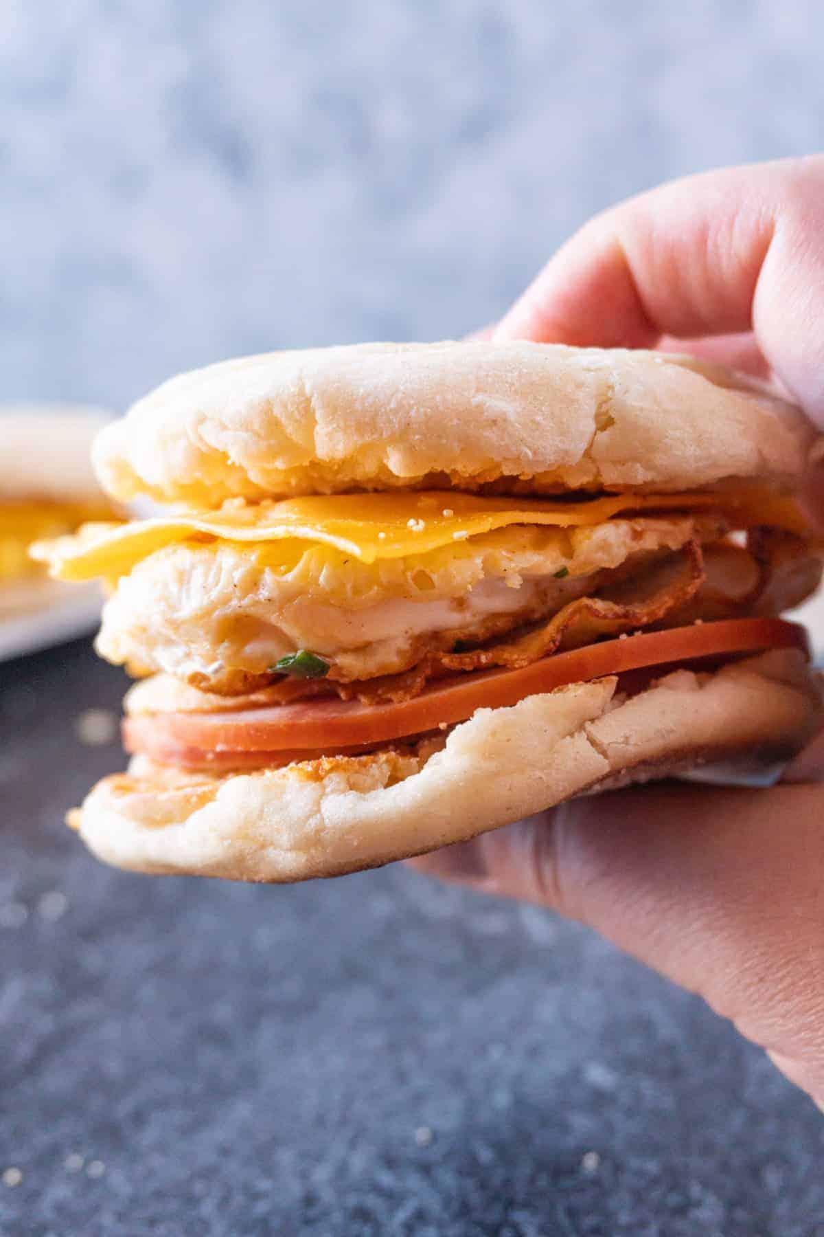 holding a fried egg breakfast sandwich