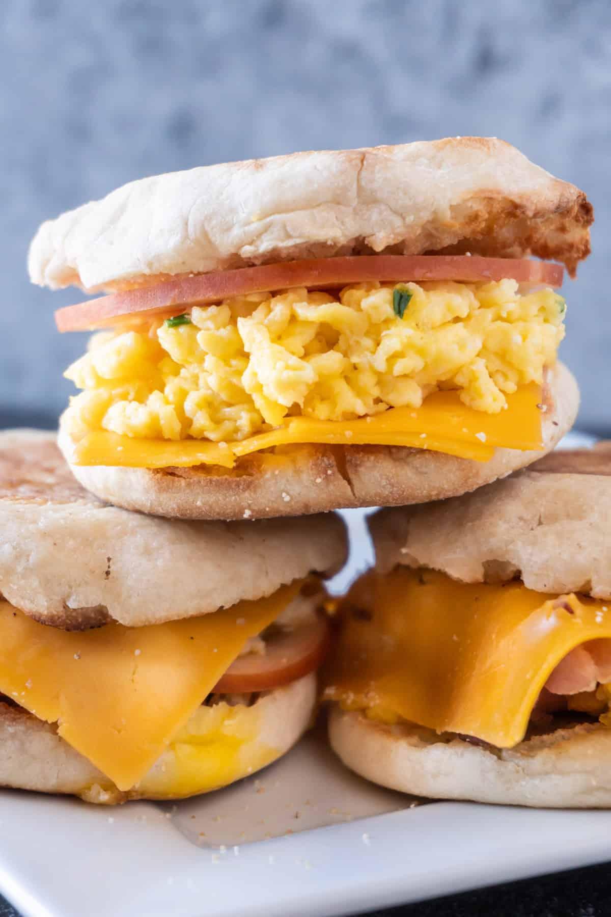 scrambled egg breakfast sandwich stacked on two other breakfast sandwiches