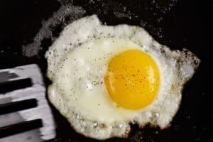 fried egg in pan before flipping