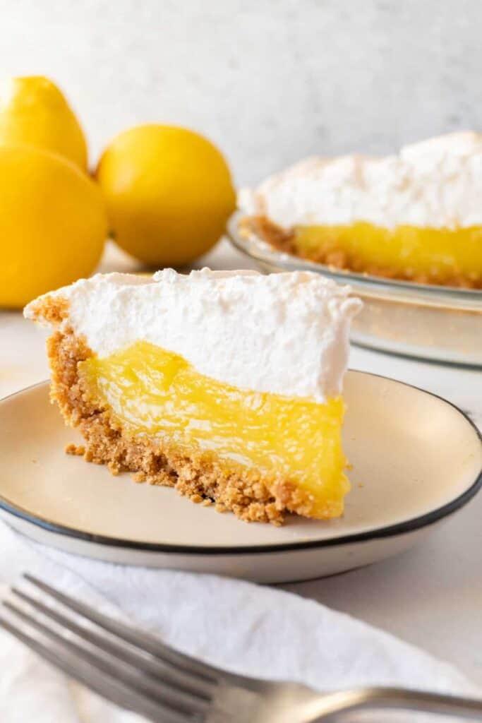 slice of lemon meringue pie with lemons and pie in the background