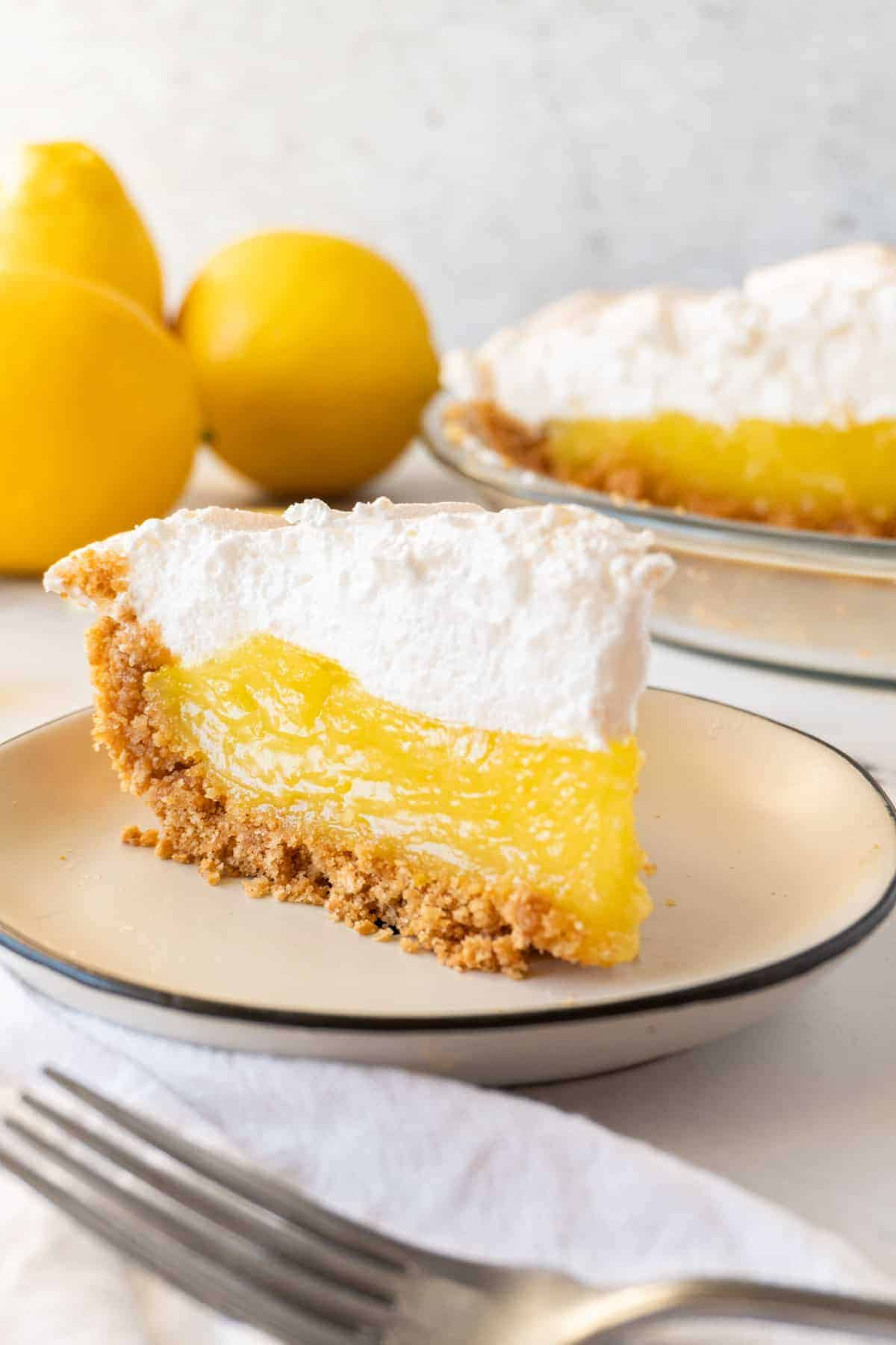 slice of lemon meringue pie with lemons and pie in the background