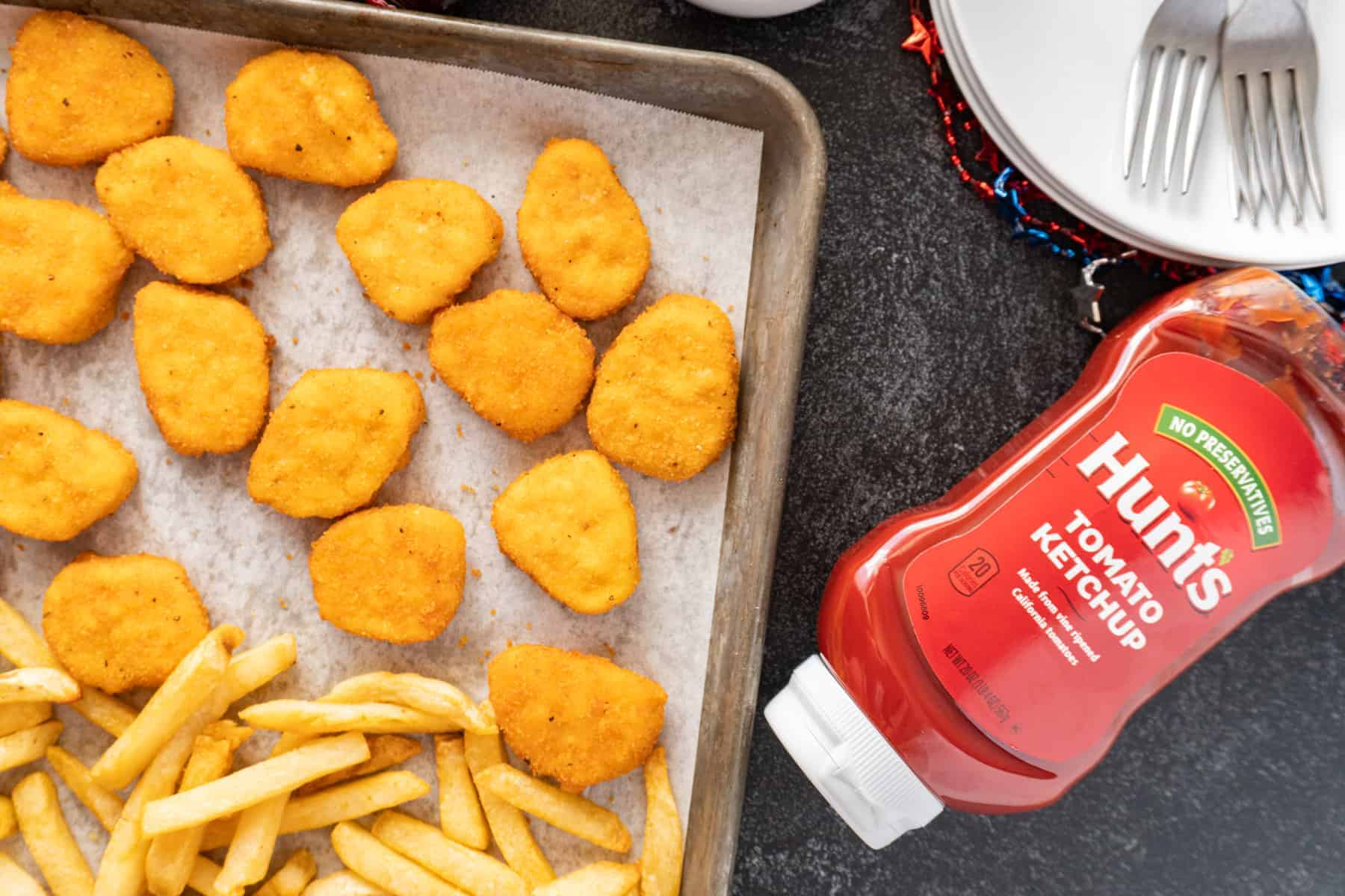 chicken nuggets and fries on baking sheet with bottle of ketchup next to it
