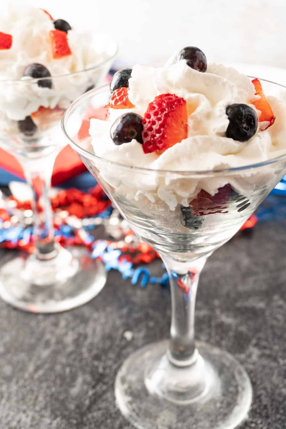 angel food cake, whipped cream, and berries in martini glass