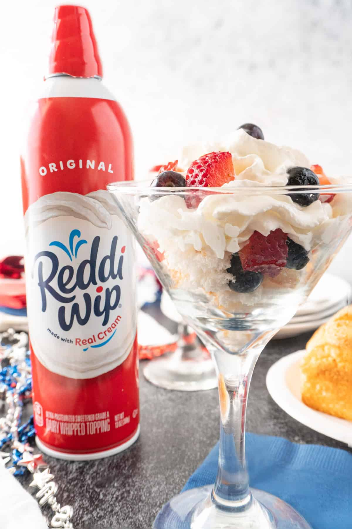 angel food cake, whipped cream, and berries in a glass with Reddi-Whip Can next to it