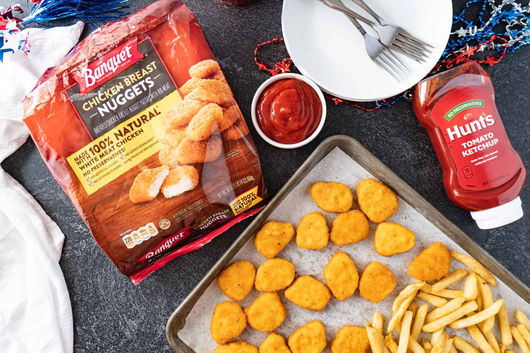 chicken nuggets on tray with ketchup bottle and chicken nugget bag nearby