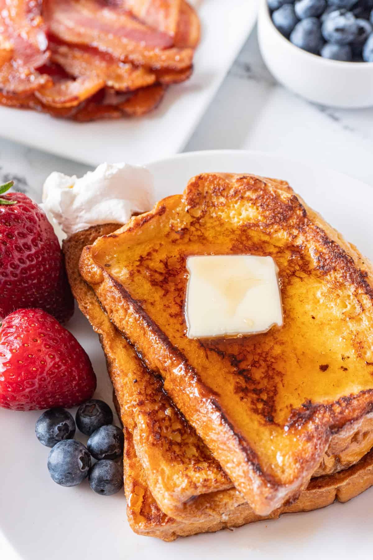 french toast with butter and berries and syrup on a plate with bacon in background