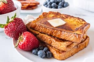 stack of french toast with butter and berries and syrup on a plate horizontal image