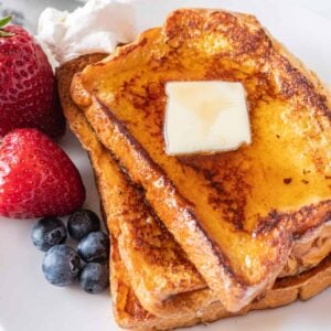 featured french toast image- french toast with butter and berries and syrup on a plate